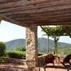 Die überdachte und weitläufige Veranda der Ferienvilla Compignano Barn mit Ausblick auf die grünen Hügel der Umgebung