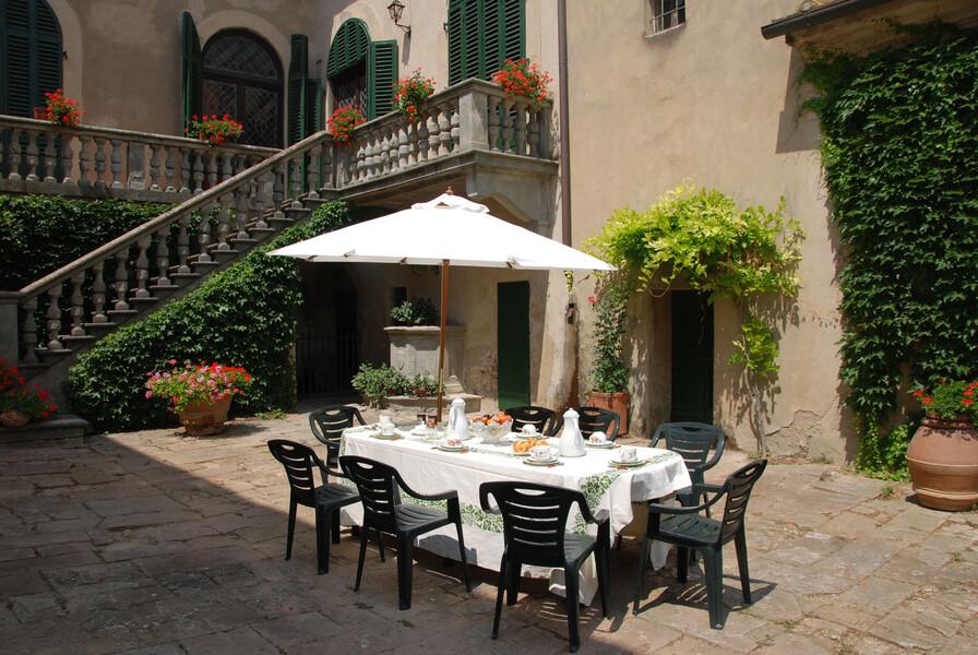 Esstisch im Innenhof der Villa di montelopio bei Pisa in der Toskana