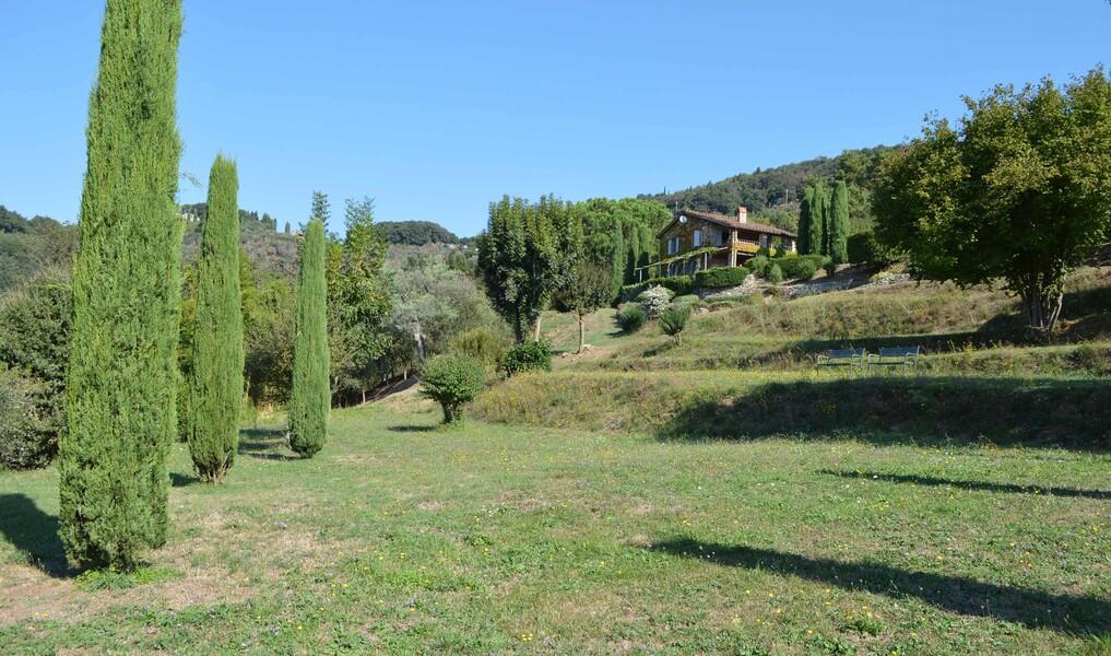 Das Ferienhaus Compignano Barn in der Toskana liegt auf einem grünen Hügel umgeben von Zypressen