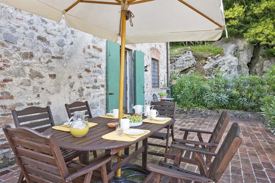 Gartentisch mit Sonennschirm im Ferienhaus casa fiora in der Toskana