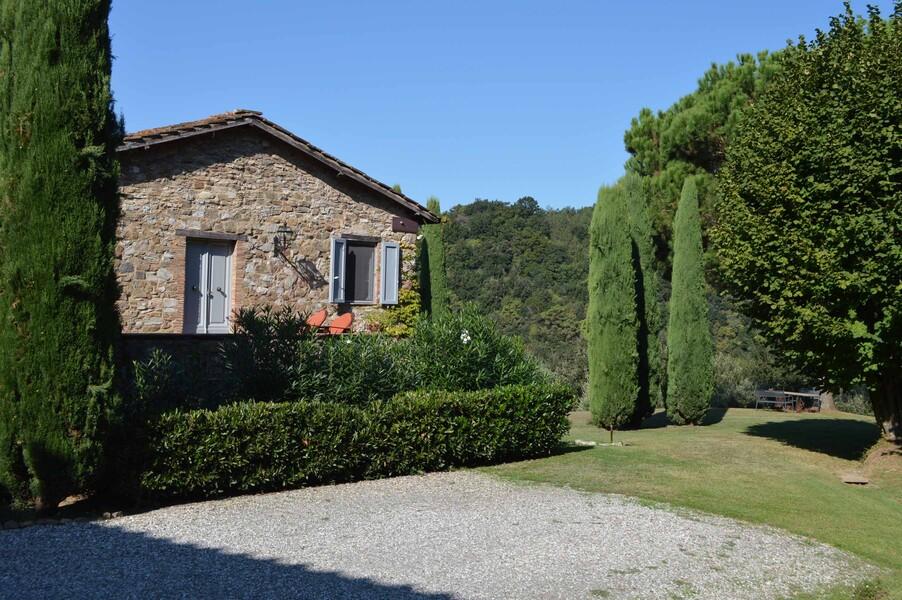 Eingangsbereich der Ferienvilla Compignano Barn mit Zypressen, Obstbäumen und Ginster