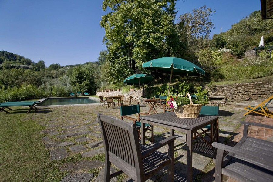 Outdoor table with private pool in the country villa Bottino in Lucca