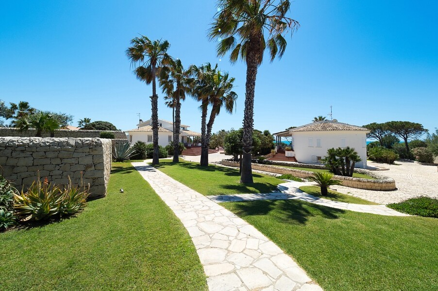 Garten mit Rasen und Palmen der Villa Maya am Meer auf Sizilien