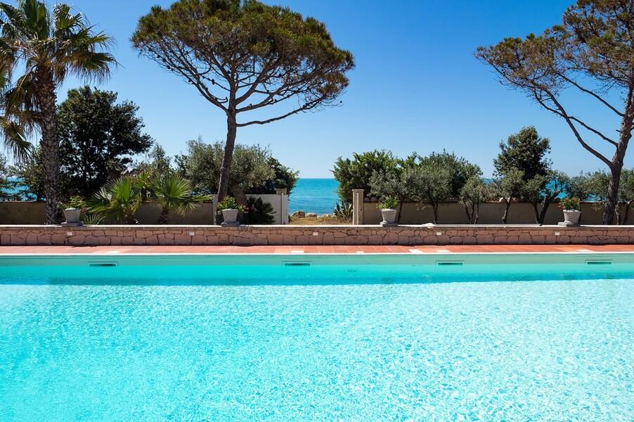 Pool mit Pinien und das Meer im Hintergrund der Villa Maya auf Sizilien